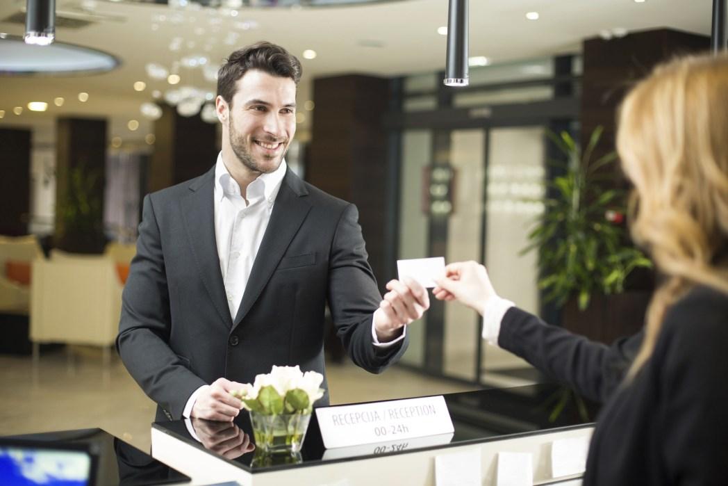 Seorang pria sedang memberikan sebuah kartu pada resepsionis hotel